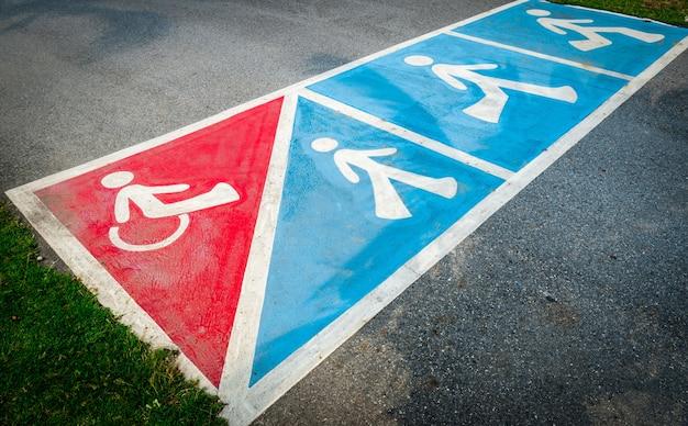 Дорожный знак на асфальтовой дороге для инвалидной коляски или пешеходной прогулки