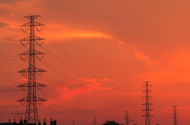 夕方には高圧電柱と送電線。日没時の電気の鉄塔。パワーとエネルギー。エネルギー資源の保護。配電所でのワイヤケーブルを備えた高電圧グリッドタワー。