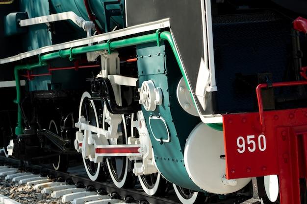 電車のクローズアップホイール。緑の赤と白の列車。アンティークヴィンテージ鉄道機関車。古い蒸気機関車。黒い機関車。古い輸送車両。鉄道輸送産業。