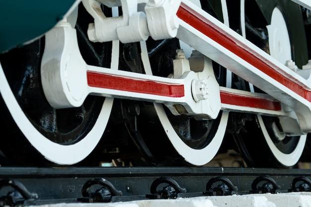 電車のクローズアップホイール。緑の赤と白の列車。アンティークヴィンテージ鉄道機関車。古い蒸気機関車。黒い機関車。古い輸送車両。