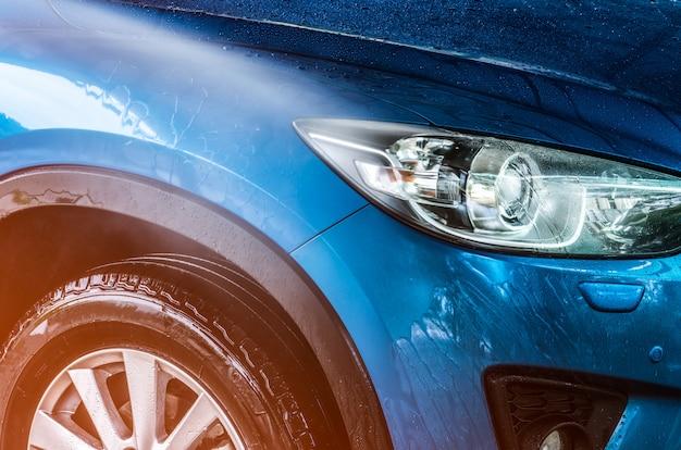Синий компактный внедорожник со спортивным и современным дизайном моют водой. автосервис бизнес-концепция. автомобиль покрыт каплями воды после очистки струей воды под высоким давлением