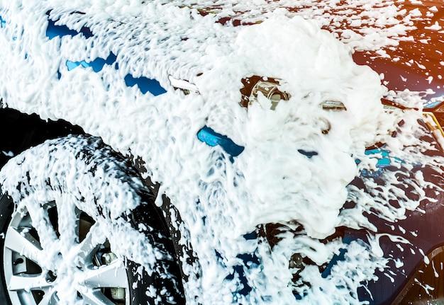 Синий компактный внедорожник со спортивным и современным дизайном, мойка с мылом. автомобиль покрыт белой пеной. автосервис бизнес-концепция.