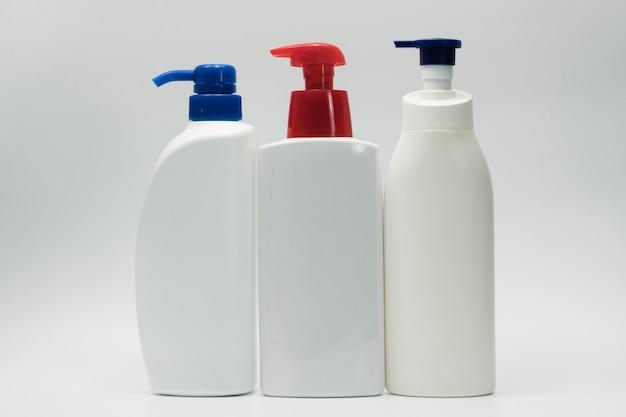 Косметическая белая пластичная бутылка при голубой и красный насос распределитель изолированный на белой предпосылке с пустым ярлыком и космосом экземпляра. бутылка для ухода за кожей. лосьон для ухода за телом. упаковка для косметической банки. бутылка шампуня.