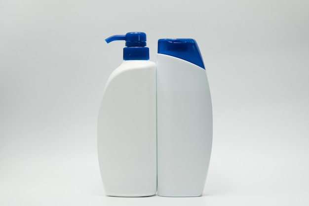 Комплект бутылки шампуня и проводника с насосом голубой крышки и распределителя на белой предпосылке с пустым ярлыком и космосом экземпляра. используйте для рекламы шампунь и кондиционер. косметическая упаковка. красота