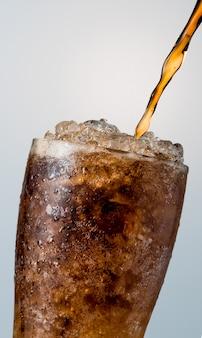 コピースペースで白い背景に分離された砕いたアイスキューブとグラスに注ぐソフトドリンクのクローズアップ。透明なガラスの表面に水滴があります。