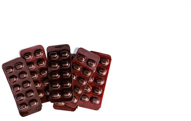 Куча таблеток таблетки медицины в светостойкой блистерной упаковки на белом фоне. витамины и минералы в таблетках для беременных. железные стеарилфумаратные таблетки для лечения анемии.