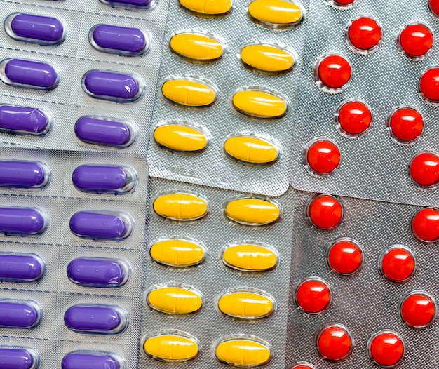 ブリスターパックでカラフルなタブレット錠剤の山。グローバルなヘルスケアのコンセプト。整形外科、鼻形成術、乳房手術後の痛みを和らげるための鎮痛剤の使用