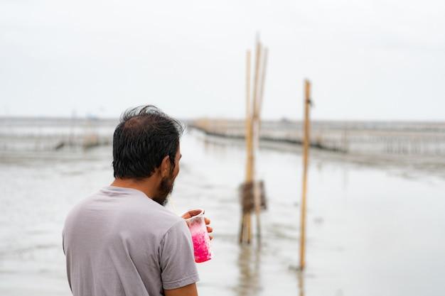 後ろの写真、ひげを生やしたショートヘアの男性、海辺でソフトドリンクを飲む