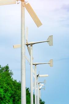 Ветротурбина с голубым небом и белыми облаками около зеленого дерева. энергия ветра в эко ветропарке. устойчивые ресурсы.
