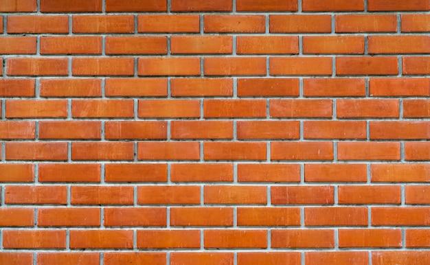 オレンジ色のレンガの壁のテクスチャ背景。テキストの背景。外装建築コンセプト。汚れたオレンジ色のレンガの壁の抽象的な背景。
