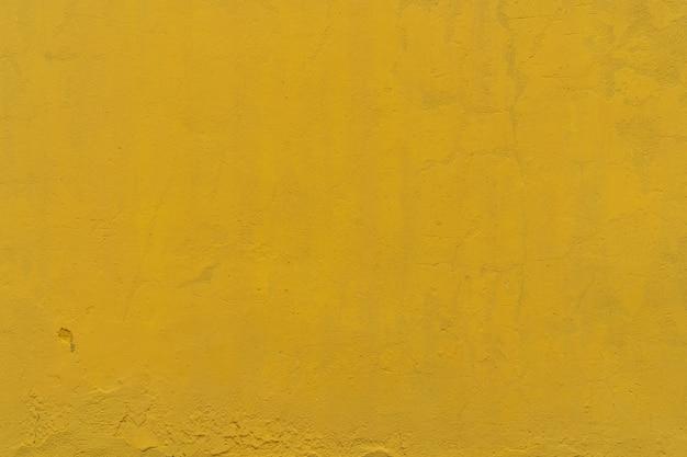 黄色の大まかなコンクリート壁のテクスチャ背景。黄色のセメントヴィンテージの抽象的な背景。テキストの空の壁スペース。