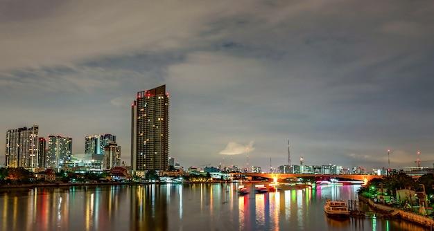 夜の川の近くのモダンな建物の街並み。近代建築のオフィスビル。夕方の空と高層ビル。川沿いの建物の夜の写真。