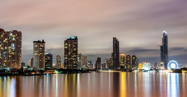 Городской пейзаж современного здания возле реки в ночное время. современная архитектура офисного здания. небоскреб с вечерним небом. ночная съемка здания набережной.