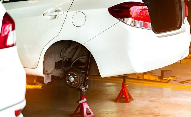 ガレージ・ワークショップに駐車している白い車が持ち上げられ、タイヤとメンテナンスが変わる