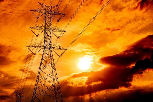 高圧電柱および送電線。日没時の電気の鉄塔。パワーとエネルギー。ワイヤーケーブル付きの高電圧グリッドタワー。
