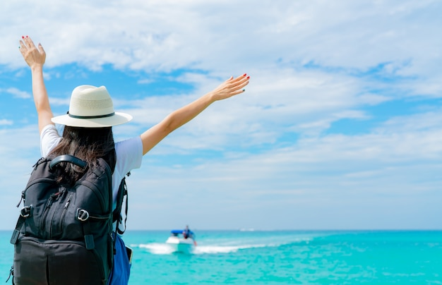 Счастливая молодая азиатская женщина в моде непринужденного стиля с соломенной шляпой и рюкзаком. расслабьтесь и наслаждайтесь отдыхом на пляже в тропическом раю. девушка в летние каникулы. летние флюиды.