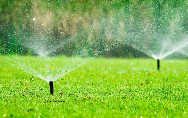 緑の草に水をまく自動芝生スプリンクラー。自動システム付きスプリンクラー。芝生に水をまく庭の灌漑システム。スプリンクラーシステムによる節水または節水。