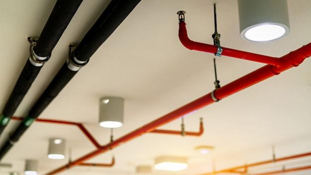 自動火災スプリンクラー安全システムと黒水冷却供給パイプ。消火。防火および探知器。赤いパイプを備えた火災スプリンクラーシステム。