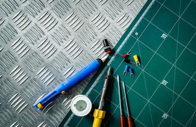 はんだ付けツール。はんだごて、はんだワイヤのスプール、ドライバー、産業用金属チェッカープレートに置かれたはんだ付けされていない絶縁スペード端子、緑色のカッティングマット。