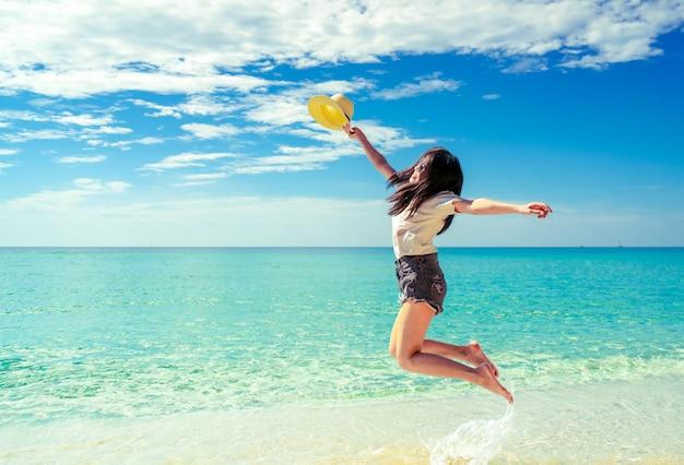 Счастливая молодая женщина в моде непринужденного стиля и соломенная шляпа скача на пляж песка.
