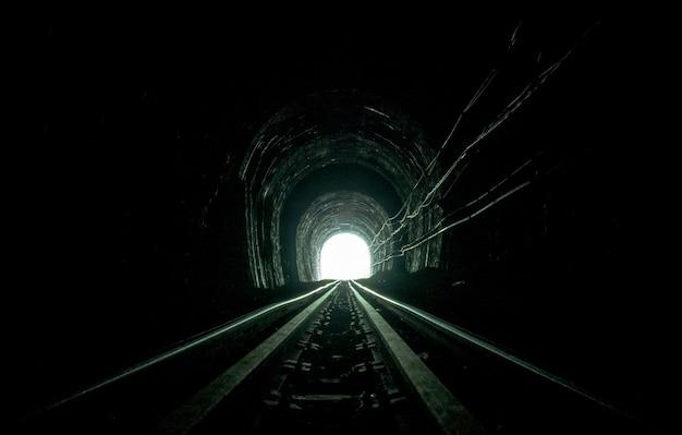 鉄道トンネル。洞窟の古い鉄道。道の終わりに人生の希望。