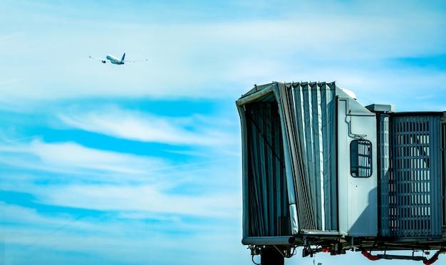 Реактивный мост после коммерческой авиакомпании взлетают в аэропорту, а самолет летит в голубое небо и белые облака. самолет пассажирского посадочного моста состыкован.