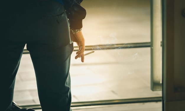 アジアの男性の手がタバコを吸う