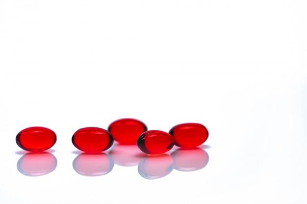 分離された赤いソフトジェルカプセル錠剤。赤いソフトゼラチンカプセルの山。ビタミンと栄養補助食品のコンセプト。製薬産業。薬局のドラッグストア。