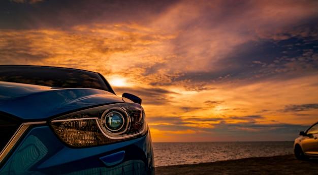 Роскошный синий внедорожник припаркован на дороге рядом с тропическим пляжем с красивым закатным небом. новый автомобиль со спортом и современным дизайном. вождение автомобиля для летней поездки. автоматизированная индустрия.