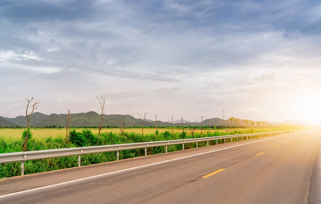 Дорога асфальта около поля зеленой травы и горы с солнечным светом. международное путешествие с голубым небом и белым облаком. проселочная асфальтовая дорога. концепция путешествия путешествие.