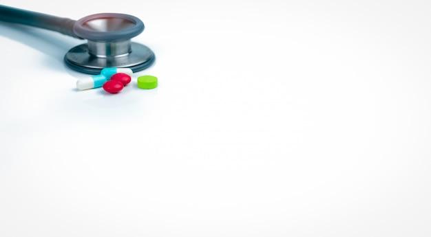 Стетоскоп, капсулы и таблетки таблетки на столе врача или медсестры. проверка здоровья.