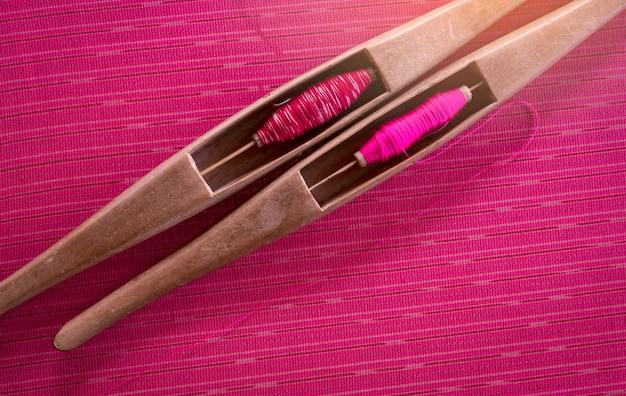 伝統的な手作りの布に織りシャトルツールでピンクの糸。テキスタイル織り。伝統的な織機とシャトルを使用した製織。