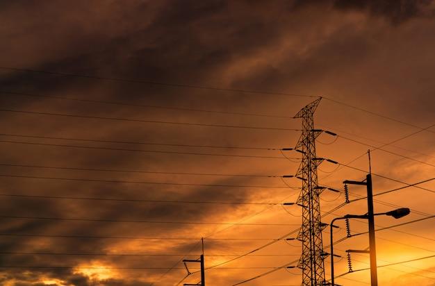 シルエットの高電圧送電鉄塔とオレンジ色の空と電線。日没時の電柱。電力とエネルギーの概念。ワイヤーケーブル付きの高電圧グリッドタワー。