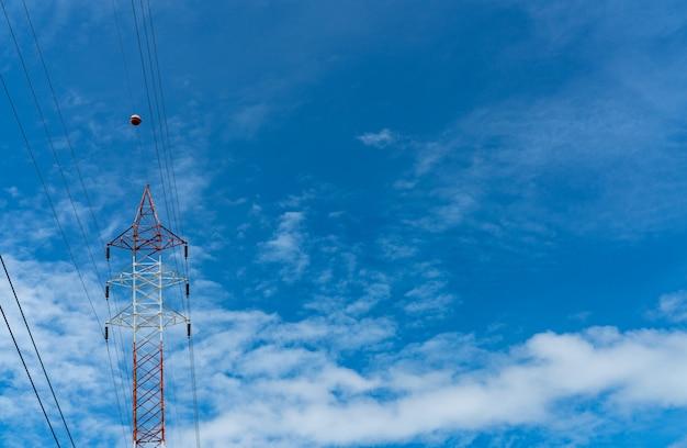 高電圧電気タワーと送電線。青い空と白い雲と電気のパイロン。電力とエネルギーの節約。ワイヤーケーブル付きの高電圧グリッドタワー。