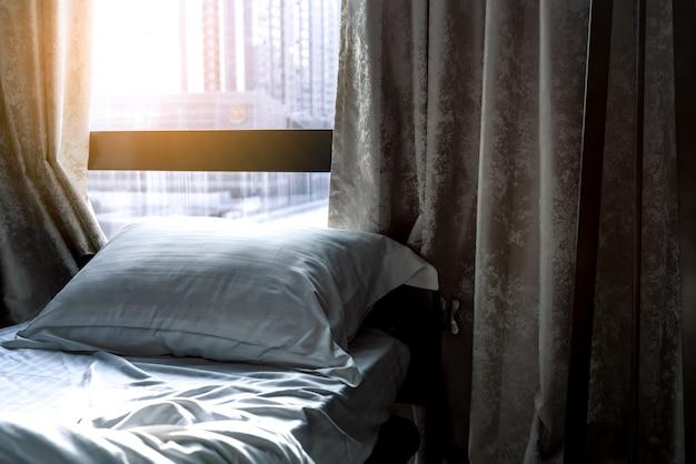 モダンなベッドルームにある白い快適なベッドと柔らかい枕。朝の日光でホテルの窓とカーテンの近くのベッド。リネンのシーツと枕カバー。