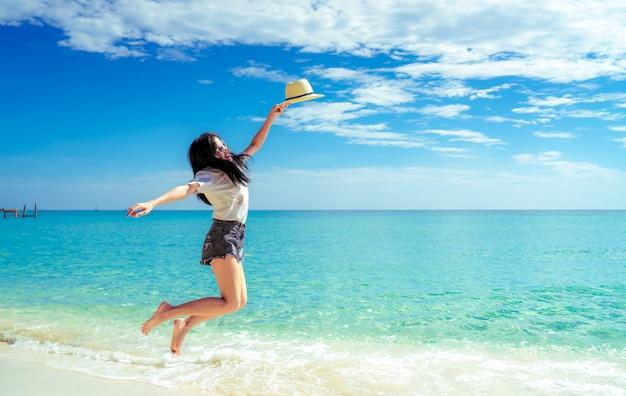 Счастливая молодая женщина в моде непринужденного стиля и соломенная шляпа скача на пляж песка. расслабьтесь и наслаждайтесь отдыхом на тропическом райском пляже. девушка в летние каникулы. летние флюиды.
