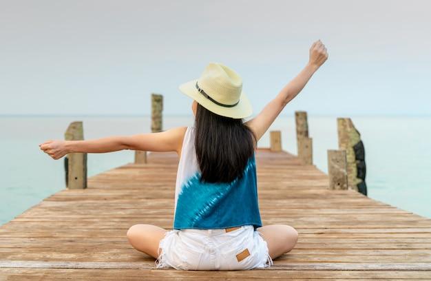 Задний взгляд счастливой молодой азиатской женщины в моде и соломенной шляпе непринужденного стиля ослабляет и наслаждается отдыхом на тропическом пляже рая. девушка на летних каникулах. летние флюиды.