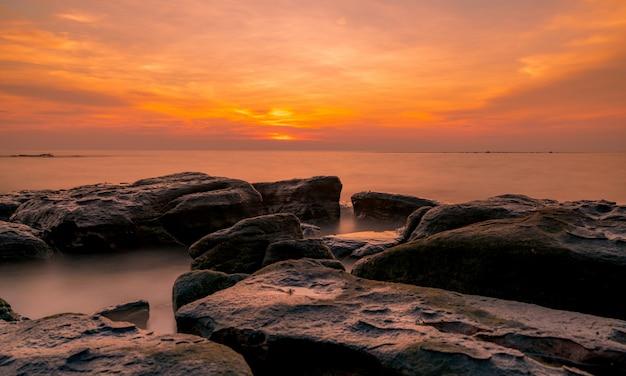 夕暮れ時の石のビーチの岩。美しいビーチの夕焼け空。夕暮れの熱帯の海