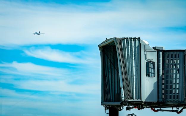 民間航空会社が空港と青い空と白い雲を飛んでいる飛行機で離陸した後のジェットブリッジ。