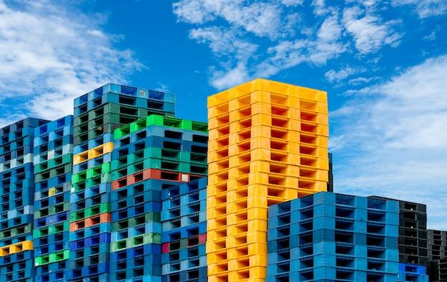 Пластиковый транспортный поддон для продажи и сдачи в аренду. промышленный пластиковый поддон укладывается на склад фабрики. концепция грузовых и морских перевозок. куча пластикового поддона.