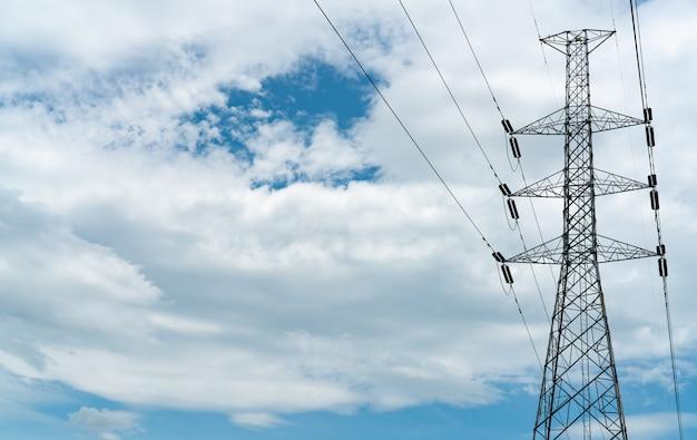 青い空と白い雲と高圧鉄塔と電線。背の高い電柱。電力とエネルギーの概念。ワイヤーケーブル付きの高電圧グリッドタワー。
