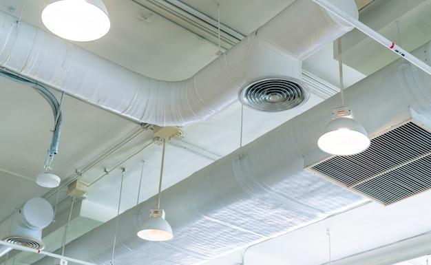 白い天井の壁にあるダクト、エアコンパイプ、火災スプリンクラーシステム。開いたライトが付いている天井ランプライト。インテリア建築コンセプト。