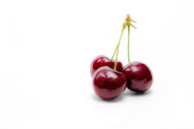 Красная вишня с изолированным стеблем. спелая красная черешня. сладкая и сочная органическая вишня. свежие фрукты для летнего десерта.