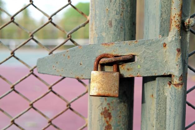 古いボルトと南京錠のドアのテニスコート
