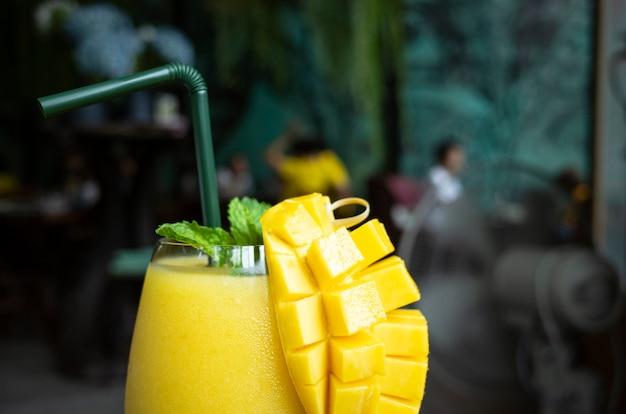 グラスにさわやかなマンゴーのスムージー、マンゴーを振る。トロピカルフルーツのコンセプト