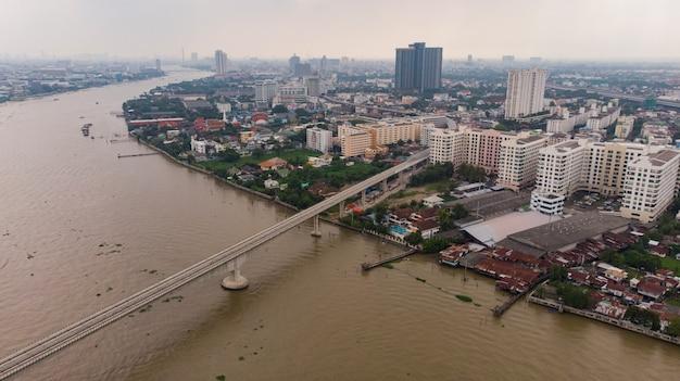 タイバンコク市のビジネス地区の側に沿って川の空中パノラマビュー