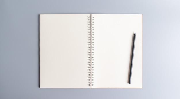 灰色の空白のノートブック紙と鉛筆の平面図です。オフィス機器、学校文具、教育コンセプト、コピースペースとバナーサイズ