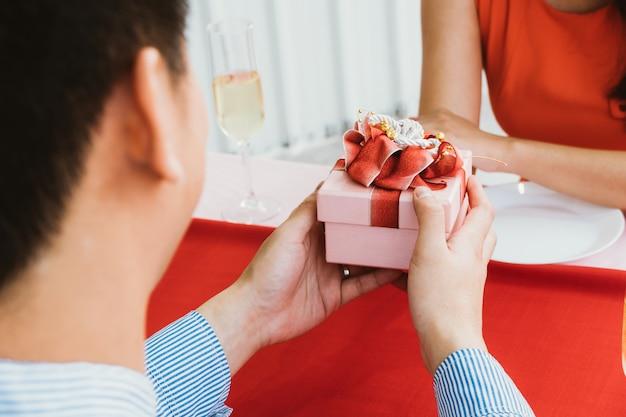 アジア人男性のロマンチックなプレゼントボックスで彼のガールフレンドを驚かせる