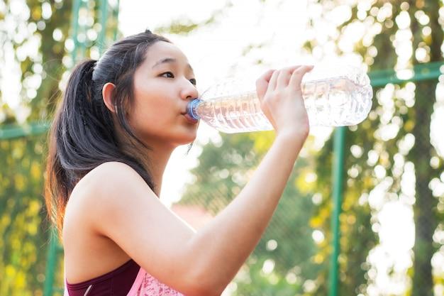 Азиатская питьевая вода женщины на комплексе напольного спорта. концепция страхования жизни здорового образа жизни