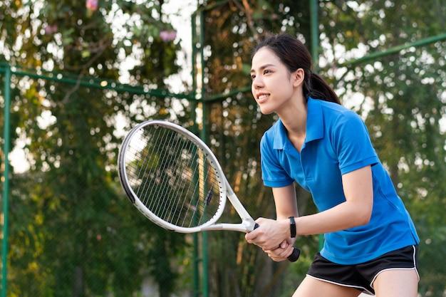 Азиатская женщина играет в теннис на открытом корте
